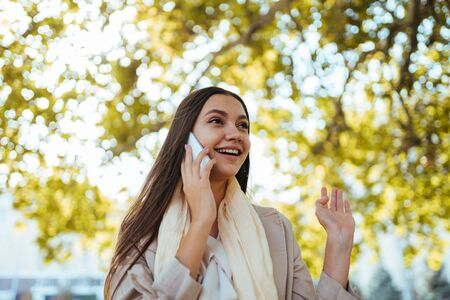 joyfully surprised girl with joy raises the phone against the background of an autumn tree