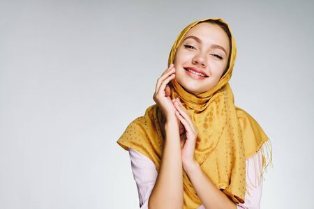 Muslim woman smiles dreamily covering her eyes and propping her cheek on her hand. gray background Stock Photo