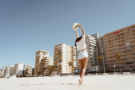 girl in shorts and a blouse with a straw hat in her raised hands over her head dancing on the sand of a beach