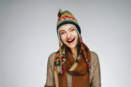 """a girl in a national hat of the peoples of the north with a warm scarf around her neck joyfully exclaims """"Wow"""" opening her mouth Zdjęcie Seryjne"""