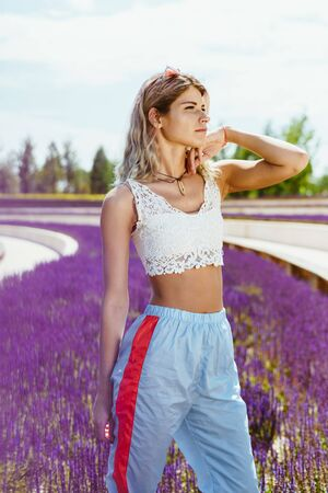 sportswoman stands in the park against a background of blooming sage and looks into the distance Stock Photo