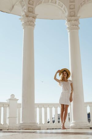 barefoot girl in white clothes and a hat stands on tiptoe among white columns and a balustrade