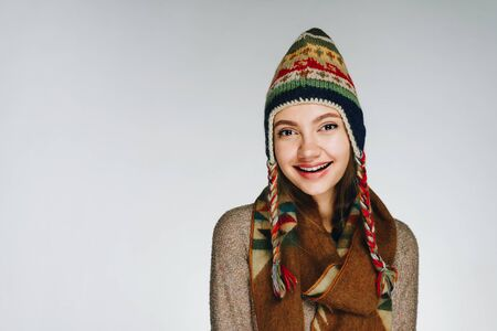 girl in a scarf and hat of the peoples of the north smiles at the camera
