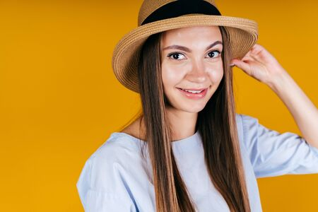 the girl with mischief in gaze and smile holds the edge of her hat with her hand. background yellow