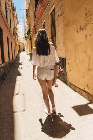 a female figure moves away along a narrow street carrying a skate in her hand. Summer, girl dressed in shorts and a shirt with bare shoulders, south of Spain