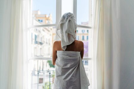 the girl after the shower in towels went to the window and opens it Foto de archivo - 135377812