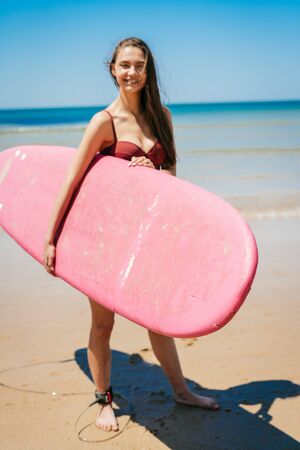 joyful contented bather carries a surfboard in her hand against the ocean Stock Photo