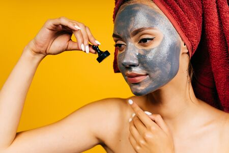 a girl with a charcoal cosmetic mask on her face holds a black chess piece in her hand, bringing it close to her cheek. towel on the head, shoulders bare Фото со стока