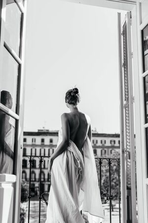 A girl resting at the hotel stands in the opening of an open balcony, wrapped in a sheet. The naked back is turned to the camera, photo black and white Foto de archivo - 135378307