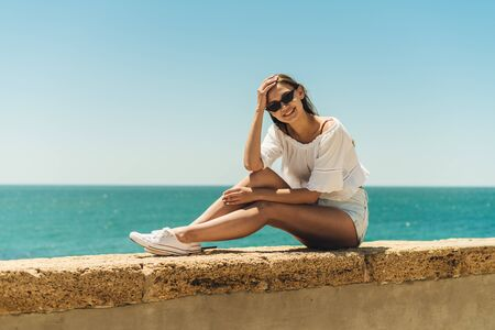 tanned girl sitting stretched out legs and resting his elbow on his knee against the background of the sea on the parapet of the embankment
