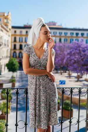 A girl stands on the balcony smoking behind the european city view