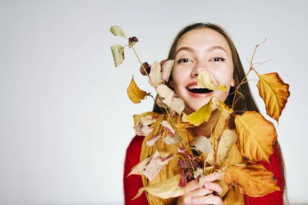 a girl with autumn branches presses them to herself and laughs joyfully