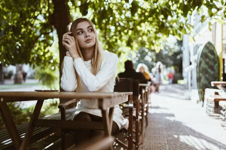 lovely blonde looks thoughtfully at the side resting her cheek on her hands in an outdoor cafe