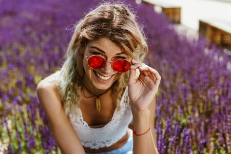 the girl is smiling broadly and holding on to the hand-arm of glasses is squatting among sage flowers Zdjęcie Seryjne