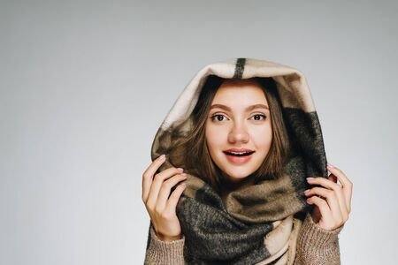 the girl built a hood from a scarf and holding it on her head with enthusiasm looks at the camera