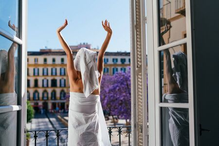 the resting woman went to the balcony after a shower and stretches her arms upward sweetly with her back to the camera Zdjęcie Seryjne