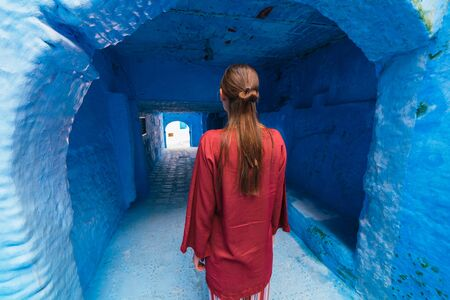 the figure of a girl in cherry-colored clothes stands in the long corridor of the blue city of Morocco Zdjęcie Seryjne