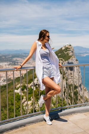 the tourist put her hands on the railing behind her and looks side down against the cliff and Gibaraaltar