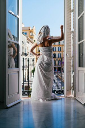 a girl in a room on the balcony stands with her back to the camera, wrapped in a sheet and a towel on her head, behind a landscape of the city