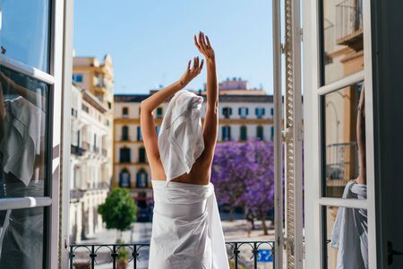 the figure of a girl from the back standing on the balcony of the room. her body is wrapped in a sheet, a towel is on her head, and with her hands she reaches up