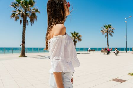 girl looking into the distance on the background of the ocean and palm trees