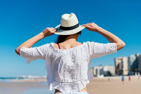 girl stands with her back to the camera, holding a hat on her head with her hands, she looks at the ocean