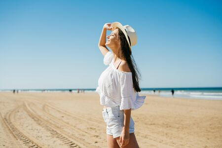 girl looking up at the sky standing on a sandy beach, people are walking far from the ocean