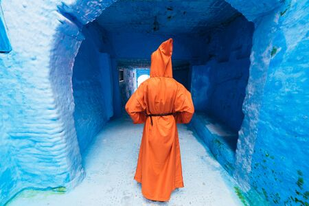 a figure in a long dress with a hood stands with his back to the camera in the corridor of the blue city of Morocco