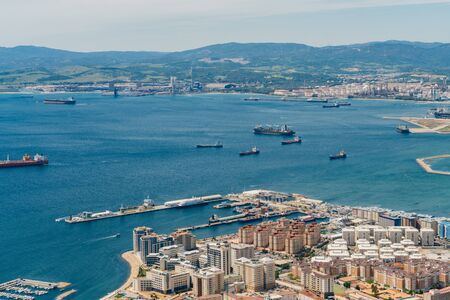 Gibraltar top view of the ocean bay with ships, coastal buildings and mountains in the distance