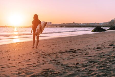 against the background of the sun setting over the horizon, a girl with a surfboard goes to the ocean water