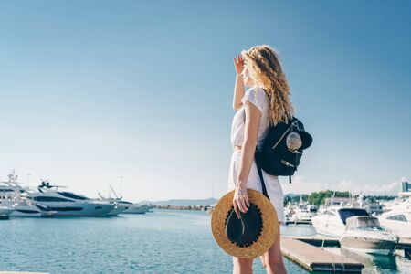 having made from a palm a visor above the eyes from the sun, a curly blonde looks into the distance while standing on the pier. she has a backpack behind her Zdjęcie Seryjne