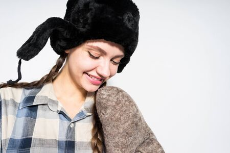 a girl in a hat with earflaps on her head in a plaid shirt holds a felt boot in her hand and looks down while smiling