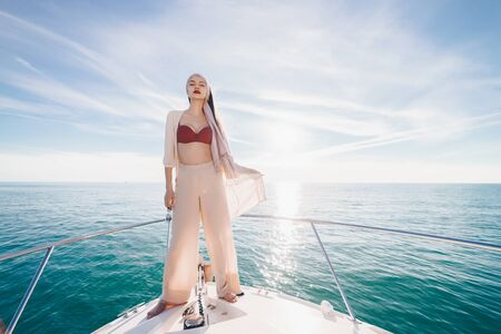a girl with glasses at the stern of the boat stands in the rays of heaven and looks into the distance