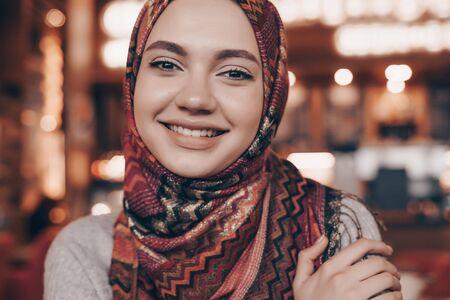 schöne lächelnde muslimische frau mit den armen umklammerten schultern