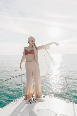 a girl in light light trousers and a bodice from a swimsuit stands on the bow of the boat, substituting a light shirt thrown over the bodice to the wind