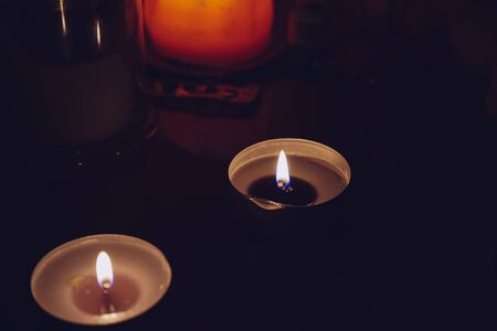 burning candles on a dark background play in flames