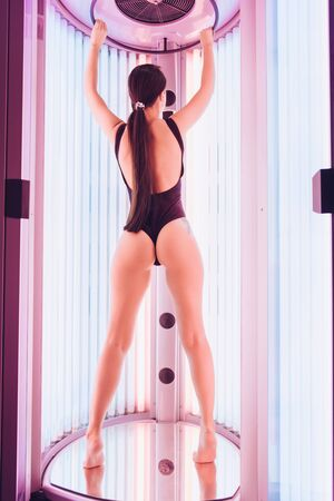 a girl in a one-piece swimsuit that opens the buttocks stands with her back to the camera in a tanning capsule Stock Photo