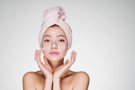 a girl with a towel on her head with shoulders applies cream to her face gently touching her cheeks with her fingers. gray background