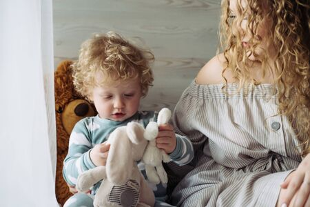 very tender scene. mom and baby are both with blond curly hair like angels