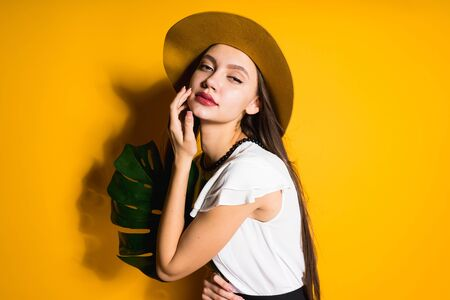 a girl with bright red lips and a picturesquely languid look in a hat with a sheet of monstera in her hand looks vzgdelom full of suffering and passion at the camera. background yellow