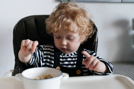 Curly blond baby, like an angel, sits at a table and touches porridge in a saucepan with a spoon 写真素材