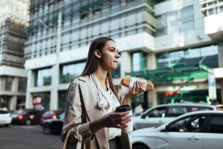 office worker at lunch break walks along the road and eats a sandwich and coffee Foto de archivo