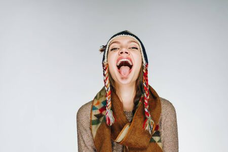 the girl in a warm hat and a warm scarf threw back her head and stuck out her tongue with a cheerful smile