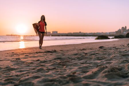 Against the backdrop of a magnificent ocean sunset, a girl is walking with a surfboard under her arm. A big city can be seen in the distance. Foto de archivo