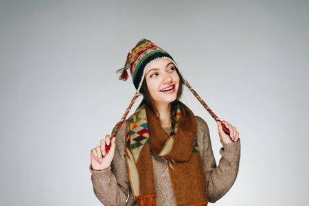 slyly squinting eyes and a cute smiling girl in a warm colorful hat holds her hands by the eyeballs background gray