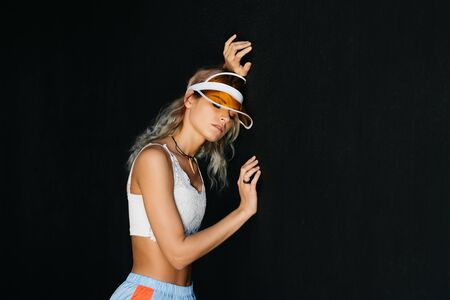on a black background, a girl in a visor and sportswear leaned her head against the wall and closed her eyes