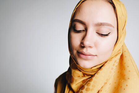 Muslim modestly dropping eyes looking down background gray Stok Fotoğraf - 147976538