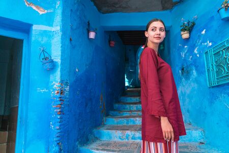 Morocco girl in national dress stands at the entrance to the tunnel with steps in the blue city.
