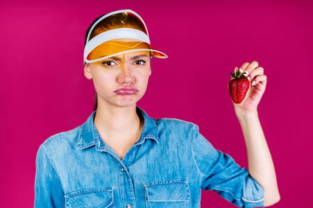 chubby and resentfully pouting her lips and frowning brows, a girl in a visor holds in her hands a strawberry berry background pink Stok Fotoğraf - 147976544