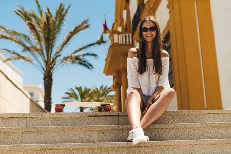 a tourist with long hair in sunglasses smiling joyfully relaxedly sits on the steps of the southern town of Spain there is a skateboard nearby